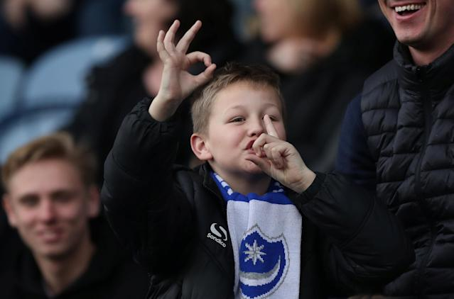"""Soccer Football - League One - Portsmouth vs Oxford United - Fratton Park, Portsmouth, Britain - March 25, 2018 A young Portsmouth fan gestures the score to the Oxford United fans Action Images/Peter Cziborra EDITORIAL USE ONLY. No use with unauthorized audio, video, data, fixture lists, club/league logos or """"live"""" services. Online in-match use limited to 75 images, no video emulation. No use in betting, games or single club/league/player publications. Please contact your account representative for further details."""