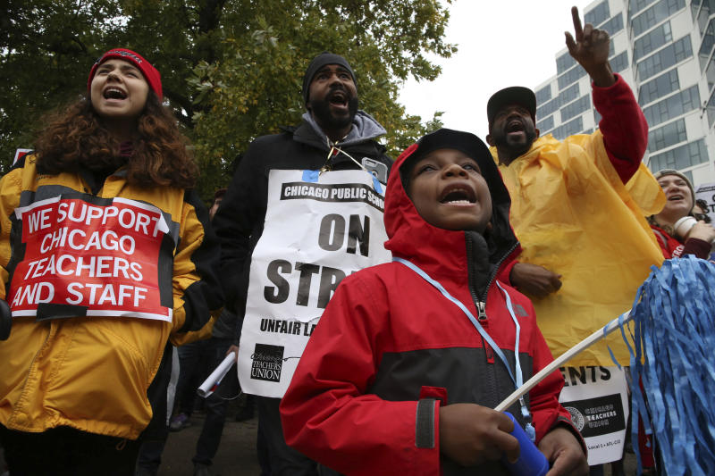 """CPS student. Bryce Kelley, 7, listens to speakers following a march by Chicago Teachers Union members and supporters through the streets of Chicago's Hyde Park neighborhood during the """"Nurse in Every School"""" Solidarity March for Justice, on Monday, Oct. 21, 2019. (Antonio Perez/Chicago Tribune via AP)"""