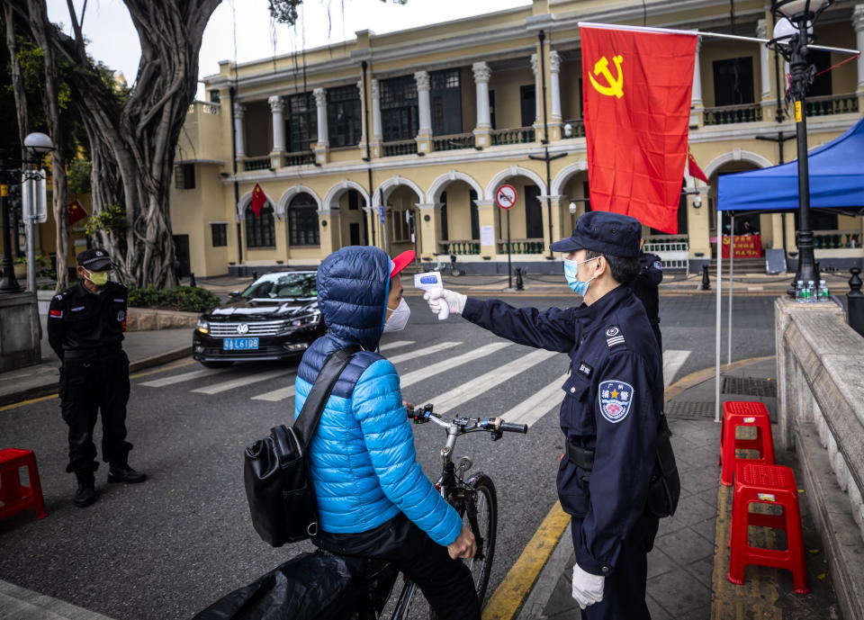 Security guards check body temperature of the people passing by on the road blockade in Guangzhou. Source: EPA/Alex Plavevski