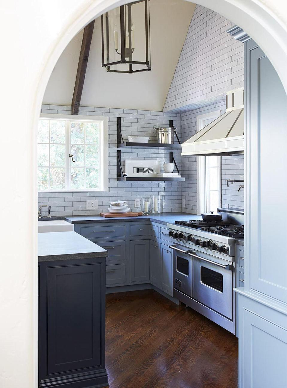 <p>Designed by Catherine Kwong, this kitchen is a contemporary classic that will age gracefully over the years. The steel gray cabinets contrast just a touch with the dark navy-gray kitchen island and cream ceilings for a balanced whole. White subway tiles and a wrought iron pendant is a great touch for a country chic kitchen. </p>