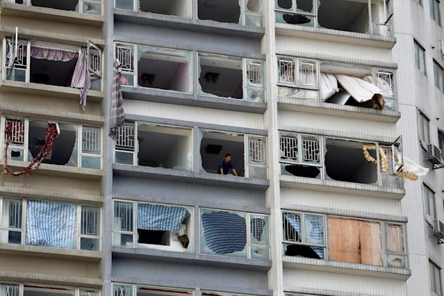 <p>A man looks out from inside an apartment where some windows have been broken by typhoon Hato in Macau, China, Aug. 24, 2017. (Photo: Tyrone Siu/Reuters) </p>