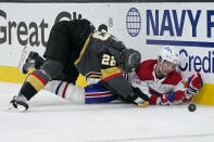 Vegas Golden Knights defenseman Nick Holden (22) and Montreal Canadiens center Jesperi Kotkaniemi (15) battle against the boards during the third period in Game 5 of an NHL hockey Stanley Cup semifinal playoff series Tuesday, June 22, 2021, in Las Vegas. (AP Photo/John Locher)
