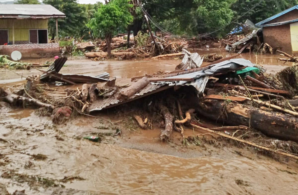 Debris litter an area hit by flash flood in East Flores, Indonesia, Sunday, April 4, 2021. Landslides and flash floods from torrential rains in eastern Indonesia have killed a number of people and displaced thousands, the disaster agency said Sunday. (AP Photo/Ola Adonara)