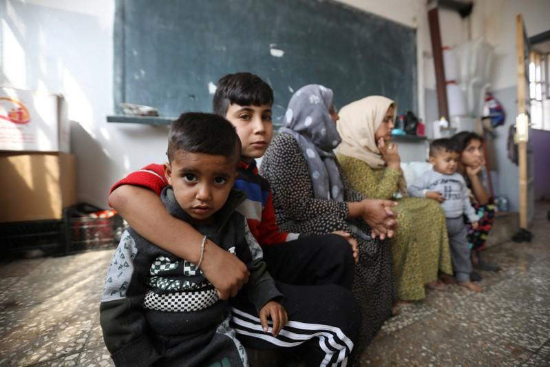 Displaced Kurdish children, who fled from violence with their family after a Turkish offensive in northeastern Syria, sit in a class roome at a public school used as shelter where they live now in Hasakah