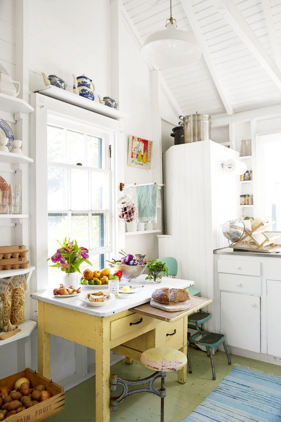<p>White walls and cabinets make way for bright and chippy painted floors and furniture, like this antique table that serves as a quirky work space. Colorful accessories stand out on built-in shelves. The overall mismatch quality solidifies the quaint cottage aesthetic.</p>