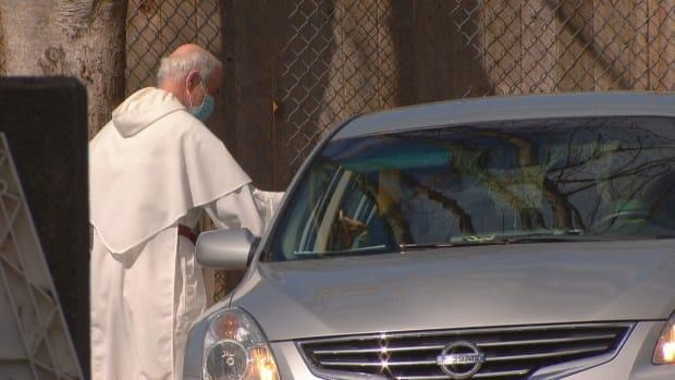 Father Guy Rivard distributes communion during a drive-thru Easter Sunday celebration at St. Mary's Catholic Church in Vancouver on Sunday. (CBC News - image credit)