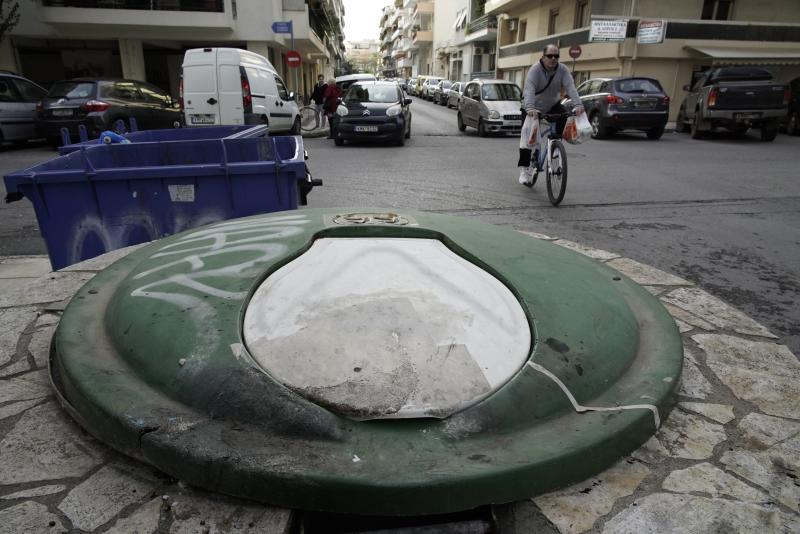 A cyclist passes near a garbage dumpster in Kalamata, southern Greece, Wednesday, Dec. 18, 2019. Greek police say they have arrested a 24-year-old foreign woman on suspicion of attempted infanticide after a passer-by found a days-old baby inside this in-ground garbage dumpster. (AP Photo/Nikolia Apostolou)