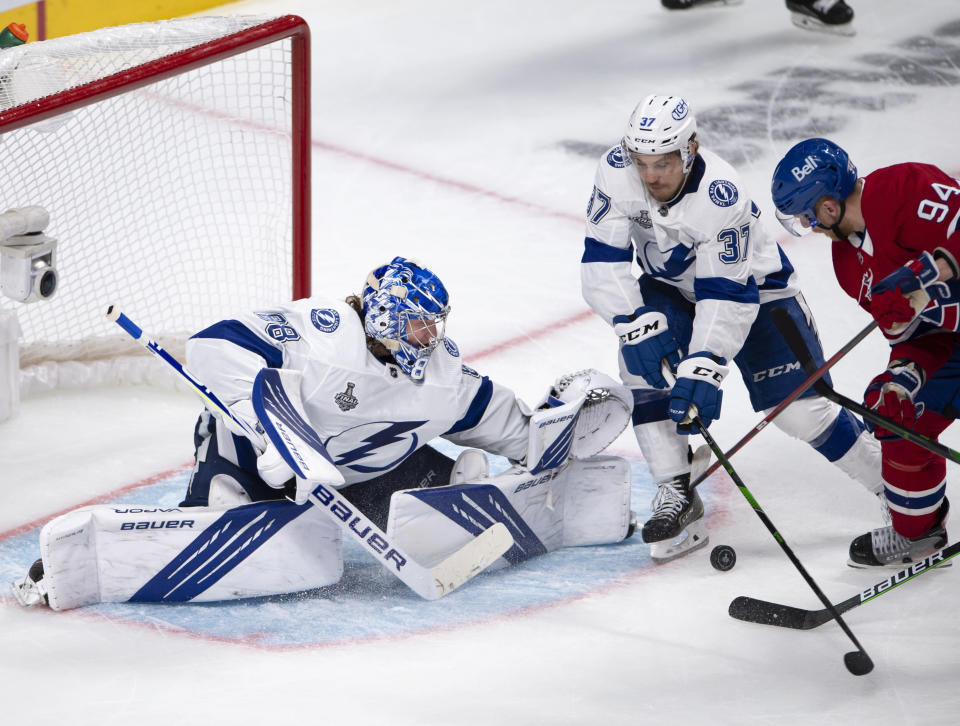 Tampa Bay Lightning goaltender Andrei Vasilevskiy (88) stops Montreal Canadiens right wing Corey Perry (94) as Lightning center Yanni Gourde (37) defends during the third period of Game 3 of the NHL hockey Stanley Cup Final, Friday, July 2, 2021, in Montreal. (Ryan Remiorz/The Canadian Press via AP)
