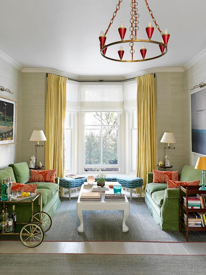 The drawing room got a new look thanks to painted flooring, reupholstered twin green sofas, and a vintage chandelier.