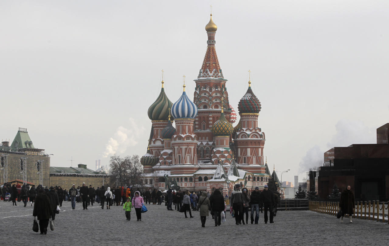 People walk in Red Square, with St. Basil's Cathedral in the background and the Lenin Mausoleum, at right, in Moscow, Russia, Saturday, March 3, 2012. Russia goes to the polls Sunday to vote in a presidential election. (AP Photo/Misha Japaridze)
