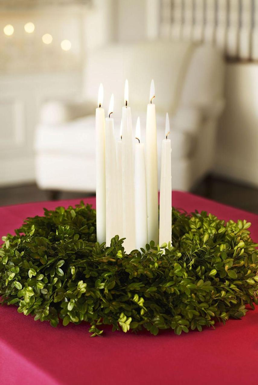 """<p>Sophisticated yet stress-free, this candlelit centerpiece will last until you ring in the New Year. Just place several snowy tapers in short candlesticks in the center of a store-bought boxwood wreath.</p><p><span class=""""redactor-invisible-space""""><a class=""""link rapid-noclick-resp"""" href=""""https://go.redirectingat.com?id=74968X1596630&url=https%3A%2F%2Fwww.etsy.com%2Flisting%2F240787306%2Fpreserved-boxwood-wreathall&sref=https%3A%2F%2Fwww.goodhousekeeping.com%2Fholidays%2Fchristmas-ideas%2Fhow-to%2Fg2196%2Fchristmas-table-settings%2F"""" rel=""""nofollow noopener"""" target=""""_blank"""" data-ylk=""""slk:SHOP BOXWOOD WREATHS"""">SHOP BOXWOOD WREATHS</a></span><br></p>"""
