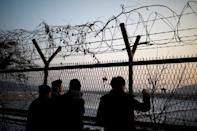 People look toward the north through a barbed-wire fence near the militarized zone separating the two Koreas, in Paju, South Korea, December 21, 2017. REUTERS/Kim Hong-Ji/Files