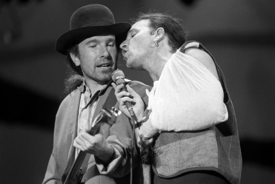 "FOXBOROUGH, MA - SEPTEMBER 22: Lead vocalist Bono, right, sings with guitarist The Edge as U2 perform at Sullivan Stadium in Foxborough, MA on Sep. 22, 1987 during the band's tour supporting ""The Joshua Tree."" (Photo by Suzanne Kreiter/The Boston Globe via Getty Images)"