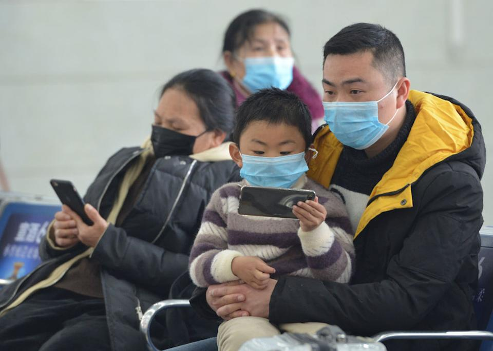 A father and son wear masks in Hong Kong airport as flights are delayed. The little boy is sitting on his father's lap holding a phone.