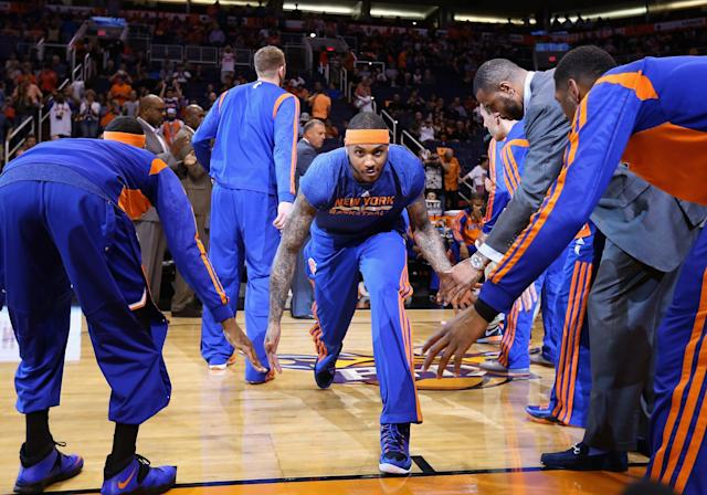 PHOENIX, AZ - MARCH 28: Carmelo Anthony #7 of the New York Knicks high fives teammates as he is introduced to the NBA game against the Phoenix Suns at US Airways Center on March 28, 2014 in Phoenix, Arizona. NOTE TO USER: User expressly acknowledges and agrees that, by downloading and or using this photograph, User is consenting to the terms and conditions of the Getty Images License Agreement. (Photo by Christian Petersen/Getty Images)