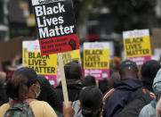 """FILE - In this file photo dated Sunday, Aug. 30, 2020, Black Lives Matter protesters hold posters as they march through Notting Hill during the """"Million People March"""" through central London. A government inquiry, by a panel of experts, has concluded Wednesday March 31, 2021, that there is racism in Britain, but it's not a systematically racist country that is """"rigged"""" against non-white people, although many ethnic-minority Britons greeted that claim with skepticism. (AP Photo/Frank Augstein, FILE)"""