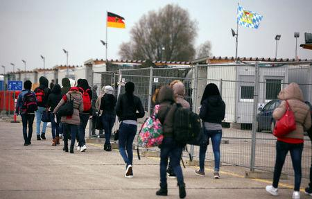 FILE PHOTO: Eritrean migrants walk after arriving by plane from Italy at the first registration camp in Erding