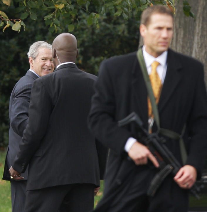 FILE - In this Oct. 28, 2008 file photo, Secret Service agents, one carrying an assault rifle, guard President George W. Bush as he walks from his limousine towards the Oval Office of the White House in Washington, shortly after a security alert on the South Lawn of the White House. The Secret Service has been tarnished by a prostitution scandal that erupted April 13, 2012 in Colombia involving 12 Secret Service agents, officers and supervisors and 12 more enlisted military personnel ahead of President Barack Obama's visit there for the Summit of the Americas. (AP Photo/Charles Dharapak, File)