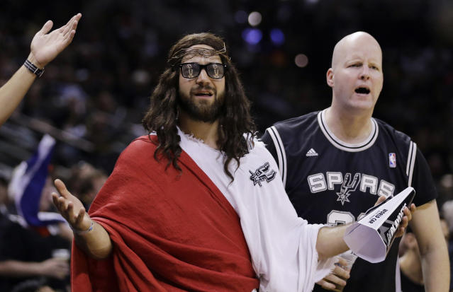 """Fans, including """"Spurs Jesus"""", center, react to a call during the second half in Game 1 of the NBA basketball finals between the San Antonio Spurs and the Miami Heat on Thursday, June 5, 2014 in San Antonio. (AP Photo/Eric Gay)"""
