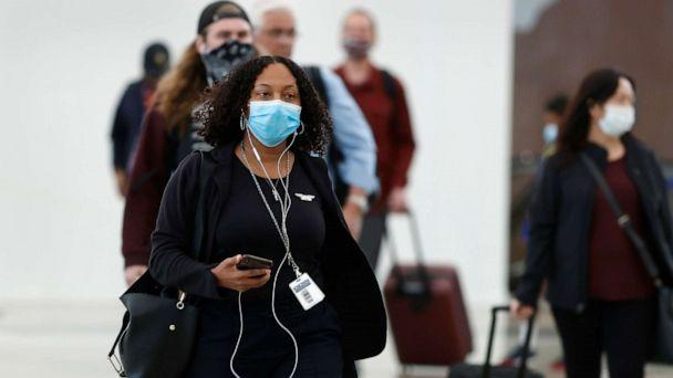 PHOTO: Passengers wear face masks as they enter the main terminal after arriving at Denver International Airport to stop the spread of the new coronavirus, April 23, 2020, in Denver. (David Zalubowski/AP)