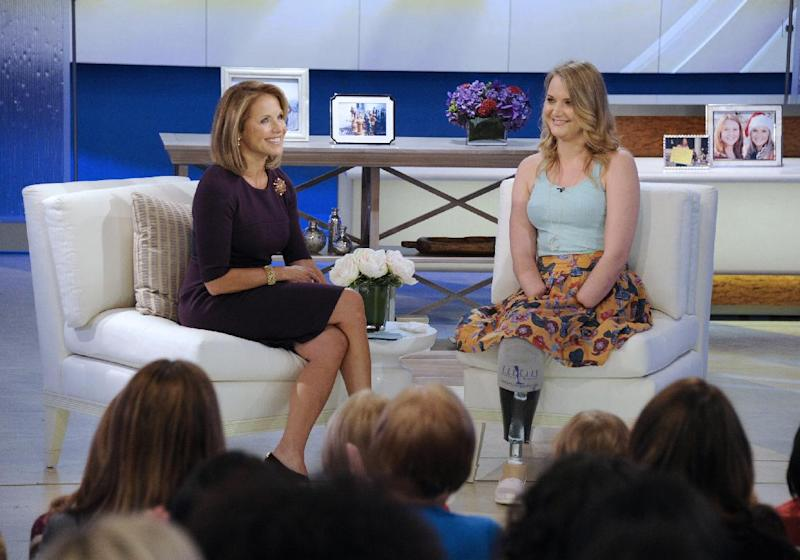 """This image released by Disney-ABC Domestic Television shows host Katie Couric, left, with Aimee Copeland, 24, of Snellville, Ga., who survived a rare fleshing-eating disease, during an exclusive interview on the new daytime talk show """"Katie,"""" Tuesday, Sept. 11, 2012 in New York. Copeland walked to the stage using a new walker. Copeland was joined in New York by her parents and sister. After Couric interviewed the family, she announced that an Atlanta-area Chevrolet dealer was in the studio to give Copeland a new minivan that will be retrofitted so she can drive it. Copeland got the infection in May after falling from a zip line and gashing her leg. Doctors had to amputate both hands, her left leg and right foot. She returned home to suburban Atlanta last week after three months in the hospital and a rehabilitation clinic. (AP Photo/Disney-ABC Domestic Television, Ida Mae Astute)"""