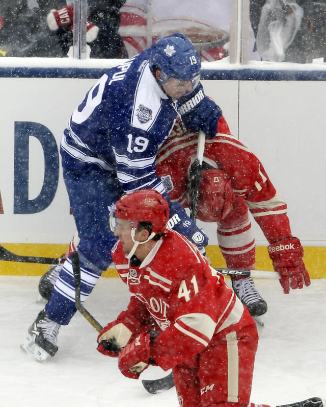 Toronto Maple Leafs right wing Joffrey Lupul (19) cross checks Detroit Red Wings forward Patrick Eaves during the first period of the Winter Classic outdoor NHL hockey game at Michigan Stadium in Ann Arbor, Mich., Wednesday, Jan. 1, 2014. Lupul received a two-minute penalty, and Eaves left the ice after hit. (AP Photo/Carlos Osorio)
