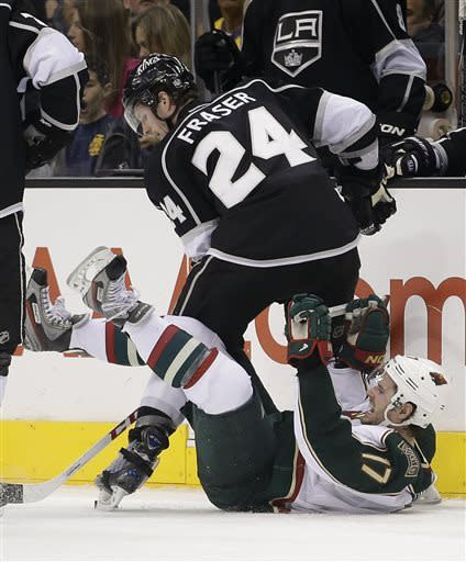 Minnesota Wild's Torrey Mitchell(17) falls to the ice as he fights for the puck with Los Angeles Kings' Colin Fraser(24) during the second period of an NHL hockey game in Los Angeles, Thursday, April 4, 2013. (AP Photo/Jae C. Hong)