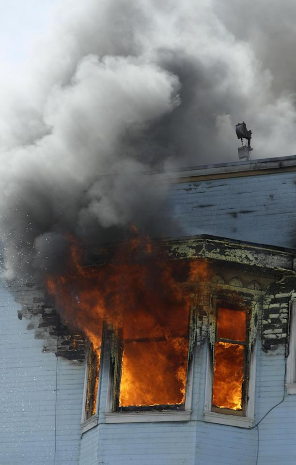 Flames engulf a window during a four-alarm fire at a residential and commercial building on the corner of Valencia Street and Duboce Avenue in San Francisco, Sunday, May 6, 2012. (AP Photo/Jeff Chiu)