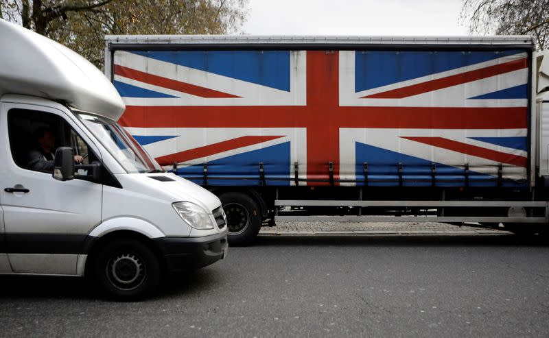 FILE PHOTO: A white van passes a lorry with the Union Flag on the side in London