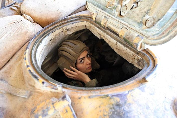 A female Syrian soldier from the Republican Guard commando battalion drives a tank during clashes with rebels in eastern Damascus on March 25, 2015 (AFP Photo/Joseph Eid)
