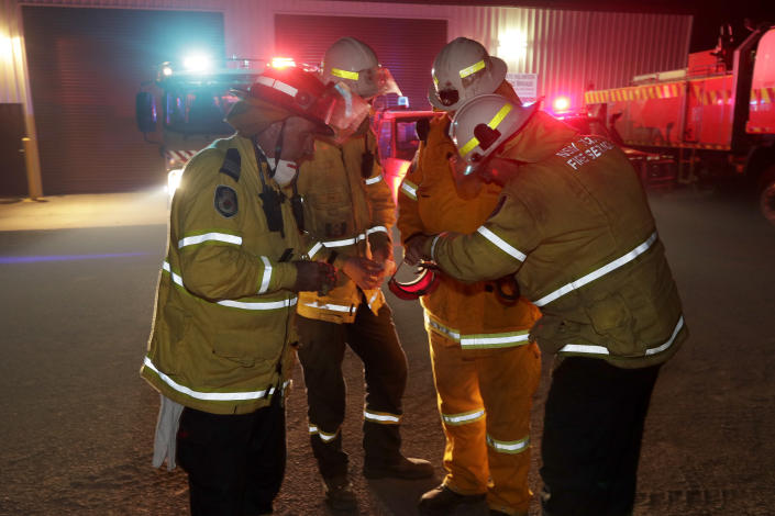 Firefighters at Burragate, Australia, gather outside the firehouse as they discuss a nearby fire threat Friday, Jan. 10, 2020. Firefighters at Burragate, Australia, gather outside the firehouse as they discuss a nearby fire threat Friday, Jan. 10, 2020. Thousands of people are fleeing their homes and helicopters are dropping supplies to towns at risk of wildfires as hot, windy conditions threaten already fire-ravaged southeastern Australian communities. The danger is centered on Australia's most populous states, including coastal towns that lost homes in earlier fires. (AP Photo/Rick Rycroft)
