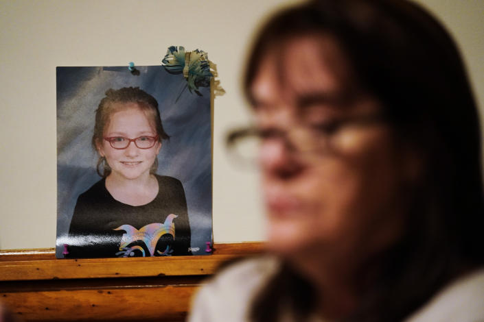 Patti Burt poses for a portrait near a photo of her granddaughter, 9-year-old Ava Lerario, in Cherry Hill, N.J., Wednesday, March 10, 2021. Burt's daughter Ashley Belson, Ava and Ava's father, Marc Lerario were found shot to death on May 26, 2020. (AP Photo/Matt Rourke)