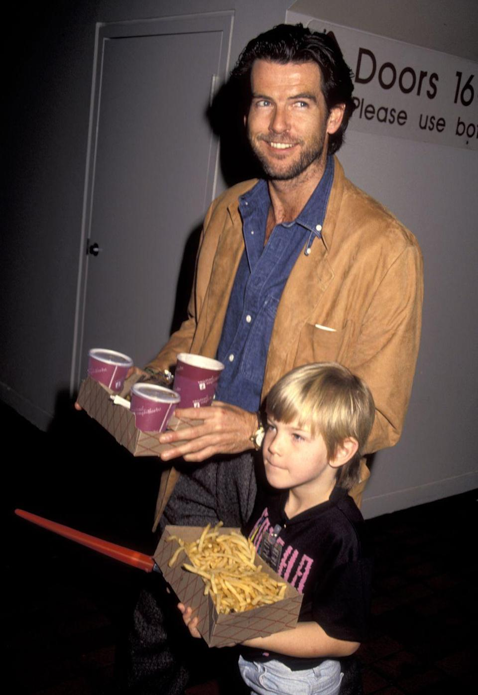 <p>Pierce Brosnan loads up on movie theater snacks with his son Sean during the premiere of <em>Teenage Mutant Ninja Turtles </em>in 1990. </p>