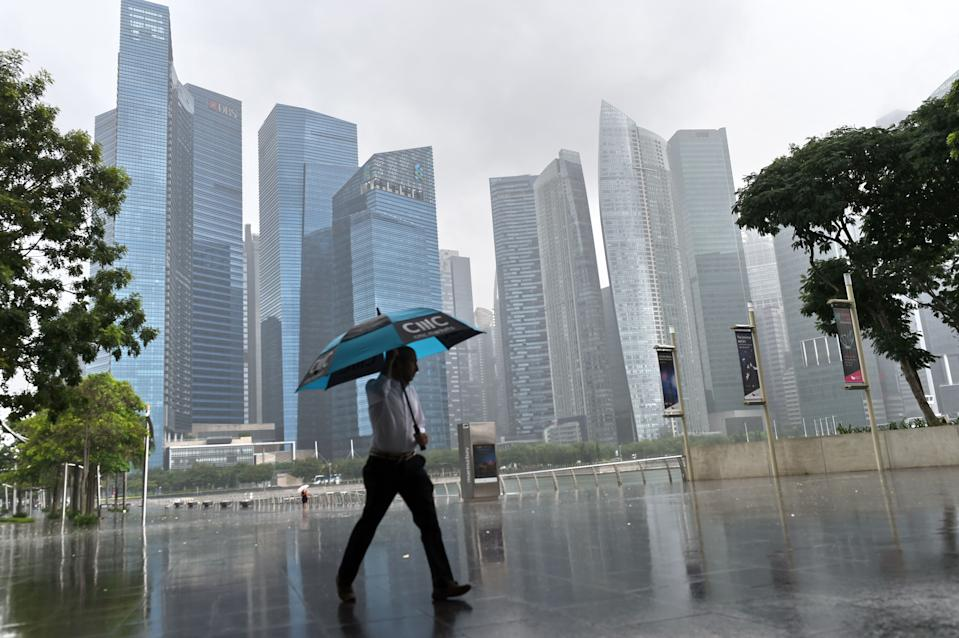 A man with an umbrella walks in the rain in Singapore on March 30, 2017. / AFP PHOTO / ROSLAN RAHMAN        (Photo credit should read ROSLAN RAHMAN/AFP/Getty Images)