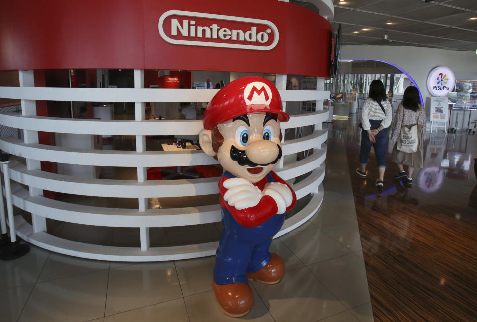 This June 19, 2018, photo, visitors walk around a figure of Super Mario of Nintendo at Panasonic center in Tokyo. Nintendo, the Japanese video game maker behind the Super Mario and Pokemon franchises, is reporting a 25 percent jump in fiscal third-quarter profit, boosted by the popularity of games for its Switch console. (AP Photo/Koji Sasahara)