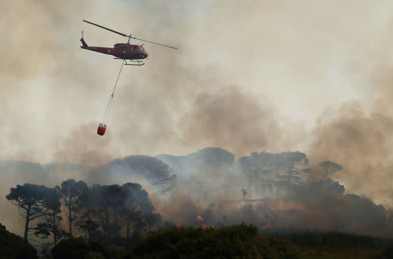 A helicopter battles to contain a bushfire that broke out on the slopes of Table Mountain above the memorial to Cecil John Rhodes in Cape Town