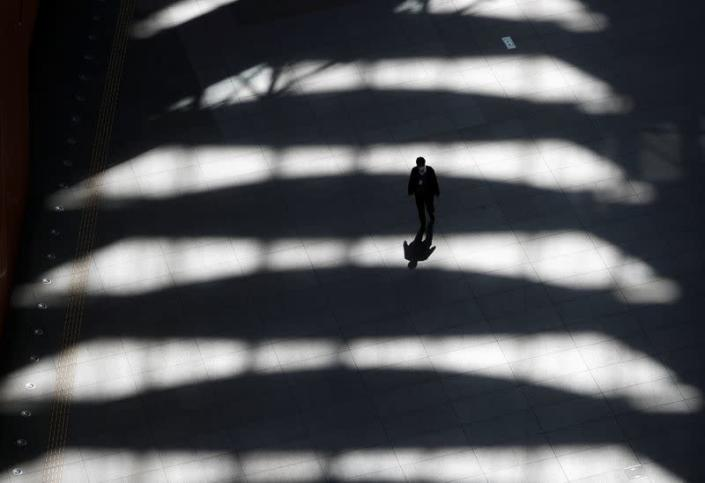 A man wearing a protective face mask, following an outbreak of the coronavirus disease, walks past inside an almost empty convention complex in Tokyo, Japan