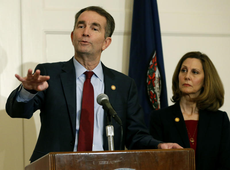 FILE - In this Feb. 2, 2019 file photo, Virginia Gov. Ralph Northam, left, gestures as his wife, Pam, listens during a news conference in the Governors Mansion at the Capitol in Richmond, Va. A law firm has completed its investigation into how a racist photo appeared on a yearbook page for Northam. Eastern Virginia Medical School said in a statement Tuesday, May 21 that the findings of the investigation will be announced at a press conference on Wednesday, May 22. Northam's profile in the 1984 yearbook includes a photo of a man in blackface standing next to someone in Ku Klux Klan clothing. Northam denies being in the photo, which nearly ended his political career in February. (AP Photo/Steve Helber, File)