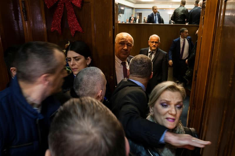 Security rush into parliamentary hall after opposition tried to prevent the vote on a bill on religious freedoms and legal rights of religious organizations in Montenegro's parliament in Podgorica