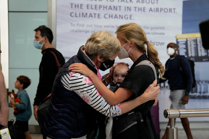 Susan Handfield meets her baby granddaughter Charlotta, held by her mother, Eva, at London's Heathrow Airport on Aug. 2, 2021, after the U.K. relaxed travel restrictions for visitors from the U.S. and European Union.