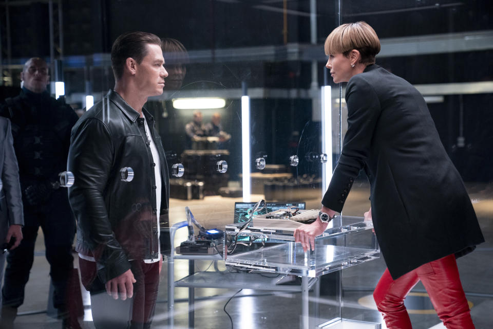 """This image released by Universal Pictures shows John Cena, left, and Charlize Theron in a scene from """"F9."""" (Giles Keyte/Universal Pictures via AP)"""