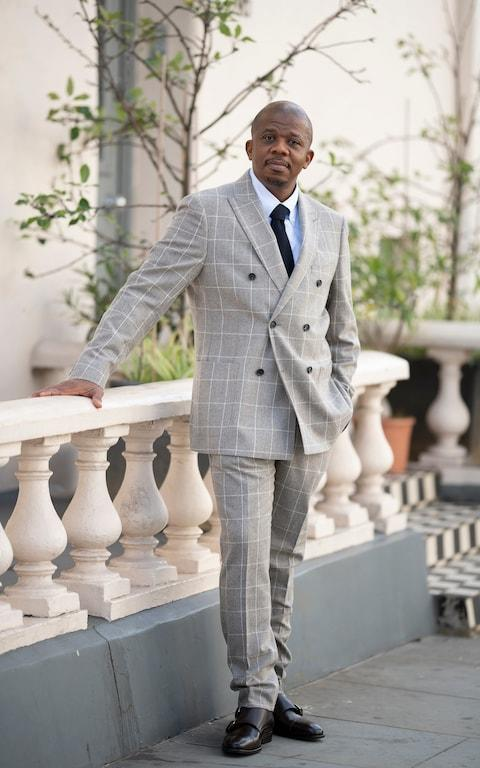 Ademola wears checked suit, shirt, knitted tie and double monk strap shoes, all from Reiss - Credit: Christopher Pledger
