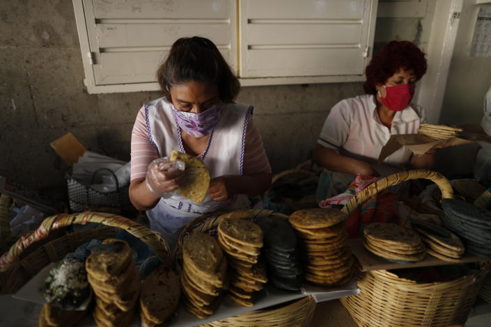 Hilda Trejo, left, and Sara Vargas Lopez wear face masks as they sell tlacoyos and sopes in a partially-open public market in the Xochimilco district of Mexico City, Friday, May 15, 2020. As Mexico moves toward a gradual reactivation of its economy Monday, the number of new coronavirus infections grows higher every day, raising fears of a new wave of infections that other countries have seen after loosening restrictions. (AP Photo/Rebecca Blackwell)