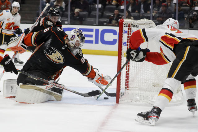 Calgary Flames center Elias Lindholm, right, scores past Anaheim Ducks goaltender John Gibson during the first period of an NHL hockey game in Anaheim, Calif., Thursday, Feb. 13, 2020. (AP Photo/Chris Carlson)