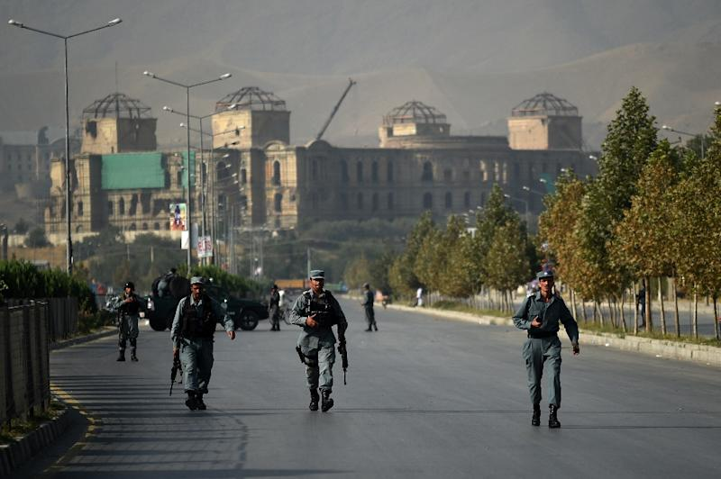Security personnel walk near the site of the elite American University of Afghanistan in Kabul on August 25, 2016, after the institution was attacked by militants