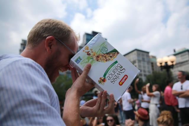 <p>A man checks out the total solar eclipse using a cereal box in Union Square, New York City, on Aug. 21, 2017. (Gordon Donovan/Yahoo News) </p>