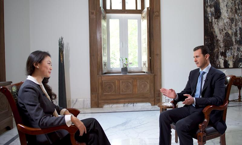 Bashar al-Assad (right) speaks with a journalist from China's Phoenix television on November 22, 2015, in Damascus (AFP Photo/)