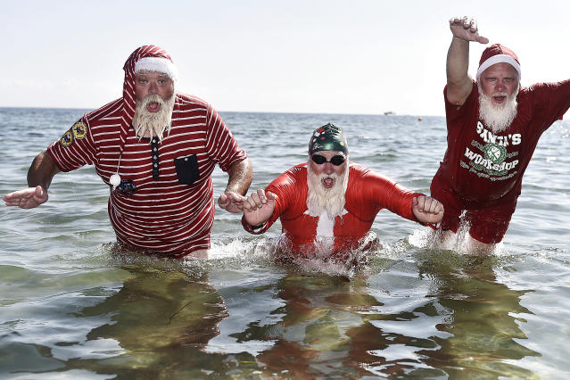 <p>Actors dressed as Santa Claus take a refreshing bath at Bellevue Beach north of Copenhagen, Denmark, on July 24, 2018, as they take part in the World Santa Congress, an annual two-day event held every summer in Copenhagen. (Photo: Mads Claus Rasmussen/Ritzau Scanpix/AFP/Getty Images) </p>