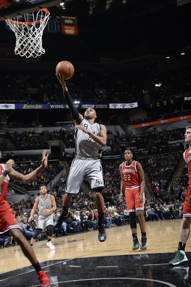 SAN ANTONIO, TX - January 19: Patty Mills #8 of the San Antonio Spurs goes up for the layup against the Milwaukee Bucks during the game at the AT&T Center on January 19, 2014 in San Antonio, Texas