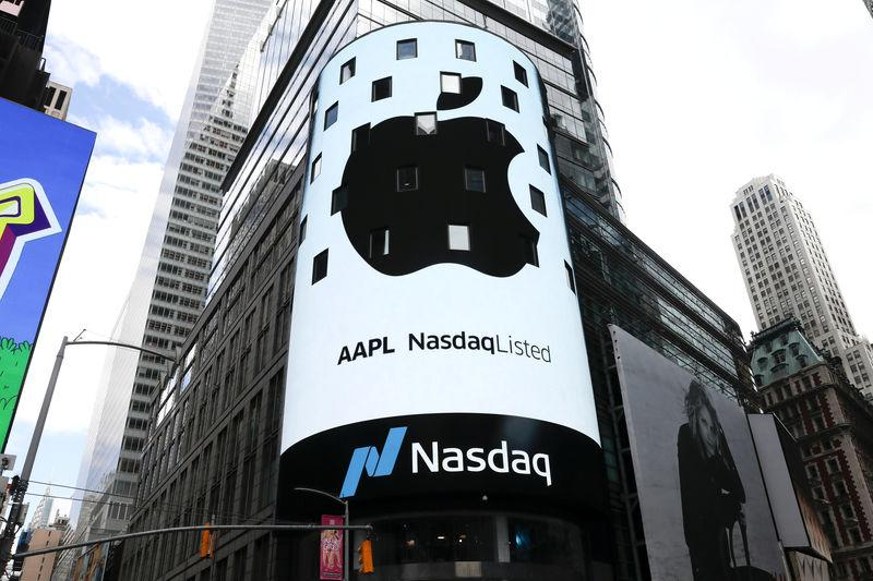 FILE PHOTO: FILE PHOTO: An electronic screen displays the Apple Inc. logo on the exterior of the Nasdaq Market Site following the close of the day's trading session in New York City